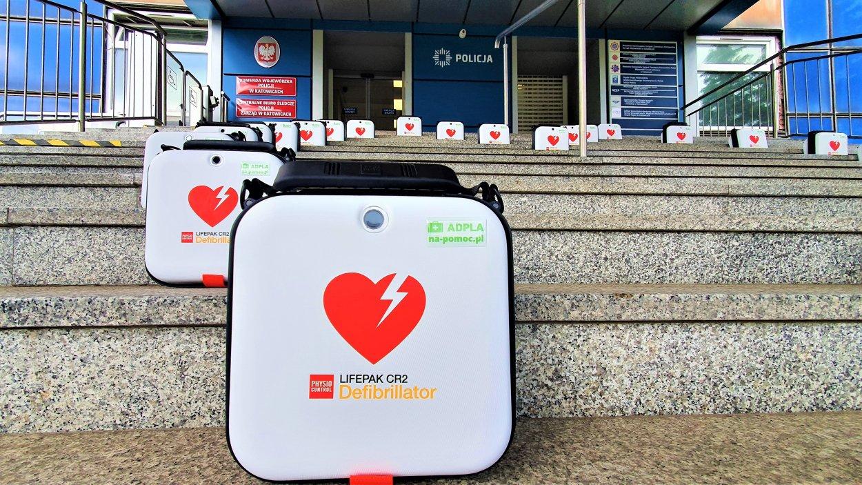 Defibrylatory ustawione w kształt serce na schodach przed wejściem do Komendy Wojewódzkiej Policji w Katowicach.