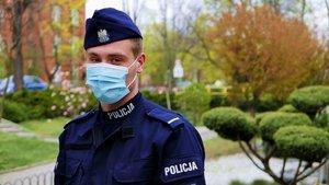 Zdjęcie kolorowe. Policjant w maseczce
