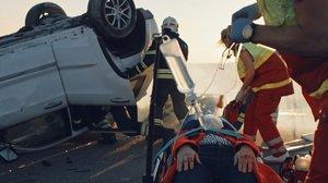 Zdjęcie kolorowe. Kadr ze spotu filmowego prezentującego miejsce wypadku drogowego. Widoczni ratownicy, strażak i poszkodowany oraz samochód.