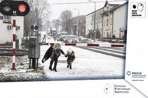 Fotografia przedstawia dorosłą kobietę przechodzącą z dzieckiem pod zamkniętym szlabanem przejazdu kolejowego.
