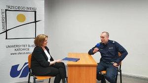 Zdjęcie koloorwe. Umundurowany policjant siedzi przy stole i wypowiada się do mikrofonu, widoczna rówineż prowadzaca romzowę siedząca w odległości z zachoaniem dystansu społecznego