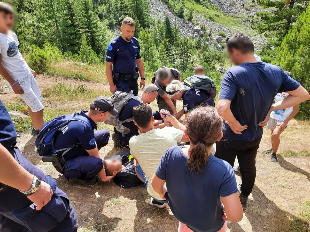 zdjęcie kolorowe: grupa polskich policjantów wKosowie schodzących zposzkodowanym zestromego górskiego zbocza