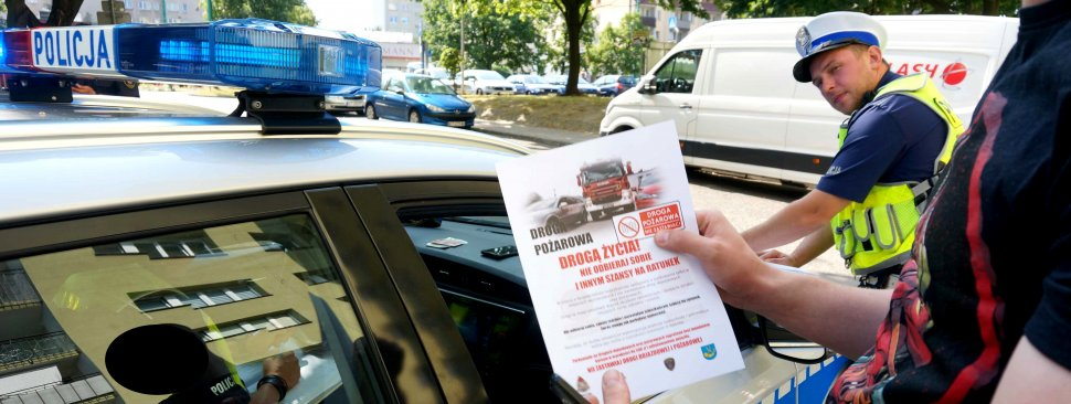 """Na zdjęciu widoczny policjant ruchu drogowego, radiowóz oraz widać ręce mężczyzny, który trzyma ulotkę akcji """"Nie odbieraj sobie i innym szansy na ratunek"""".http://tychy.slaska.policja.gov.pl/k27/informacje/wiadomosci/268300,quotBezpieczna-droga-do-szkolyquot-w-Tychach.html?sid=b4dfe4ad88895659da6d8ac9a0f8d945"""
